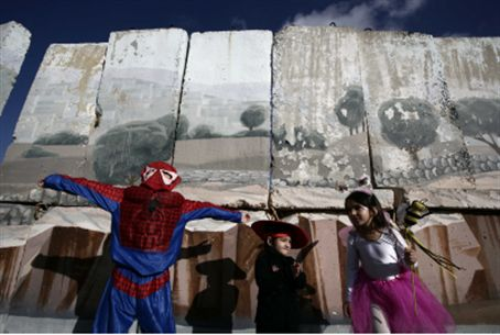 Children in Purim costumes next to Gilo wall