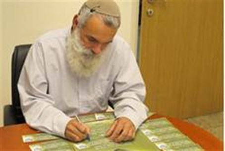 Rav Ronsky signs the card.