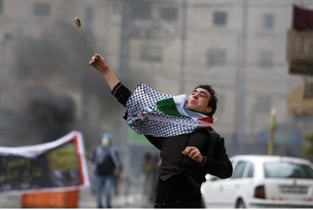 An Arab throws stones in Saturday's riots