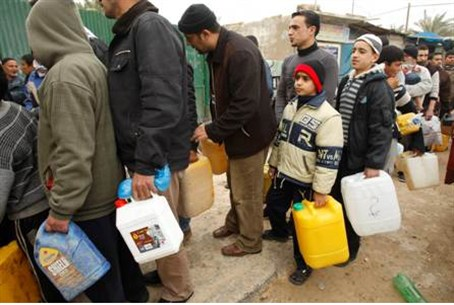 Gaza Arabs wait to fill containers with fuel