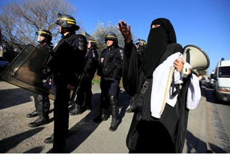 Veiled Muslim protests police raid on terror