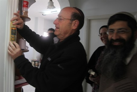 MK Schneller places mezuzah on new Hevron Jew