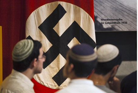 Jews stand in front of swastika at Yad Vashem