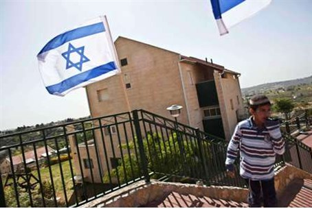 A boy walks near Israeli flags in Ulpana