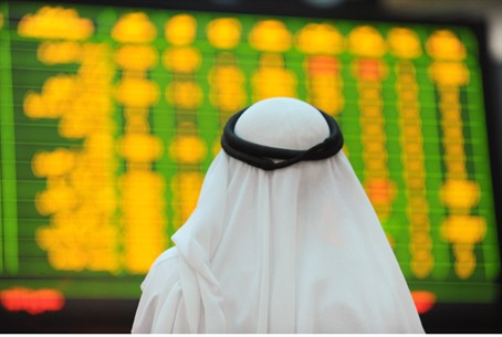 An Arab investor looks up at electronic board