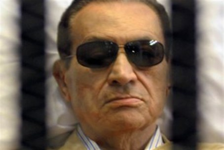 Mubarak sits inside a cage in a courtroom