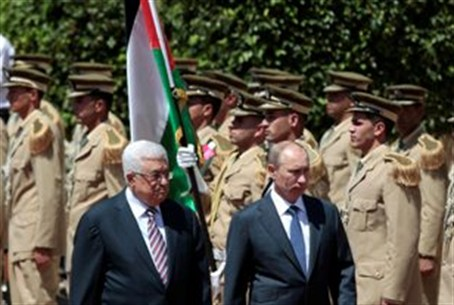 Abbas and Putin walk past an honor guard in