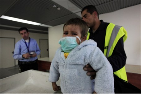 Sick Arab child, father at Gaza crossing.