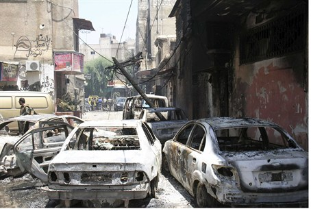Burnt cars are seen on a street at al-Midan n