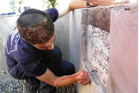 Bnei Akiva volunteer repairs tombstone