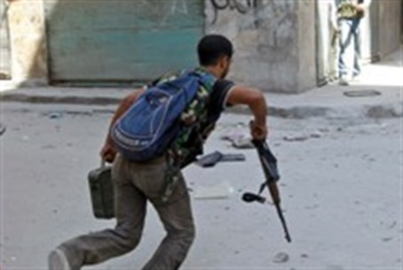 Free Syrian Army fighter runs across a stree
