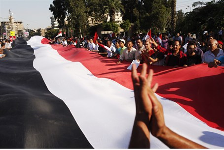 Anti-Morsi protesters hold a large Egyptian f