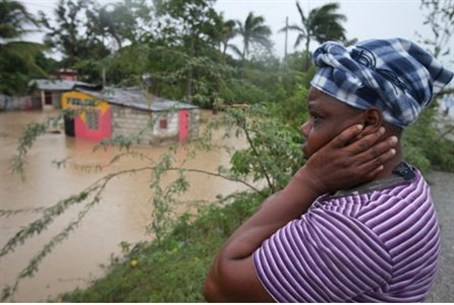 A woman surveys the damage of flooding to her