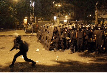 Riot policemen take cover from stones thrown
