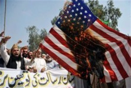 Pakistani Muslim protesters burn a US flag du