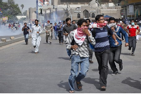 Rioters run from tear gas in Karachi