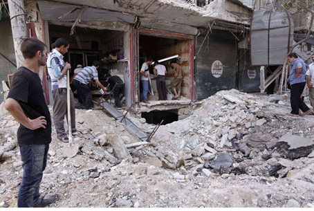 Civilians view debris from Syrian gov't air s