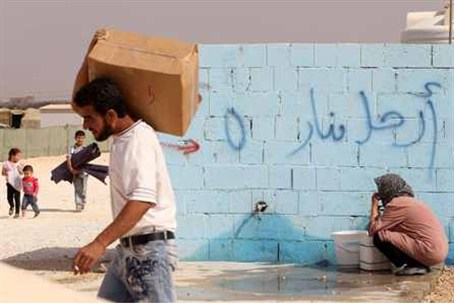 A Syrian refugee collects water at a refugee
