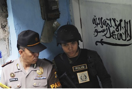 Indonesian police stand guard outside house o