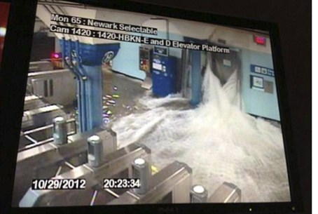 Flood waters rush into a PATH train station i
