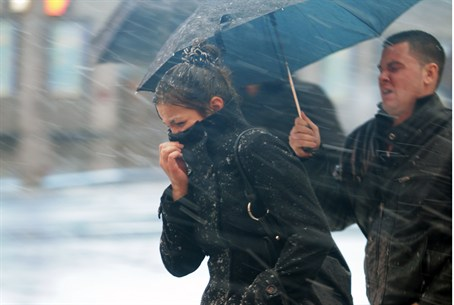 People walk through the wind and snow at New