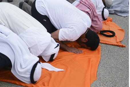 Kuwaiti protesters pray before marching