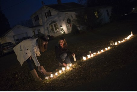 Residents light candles in their front yard f