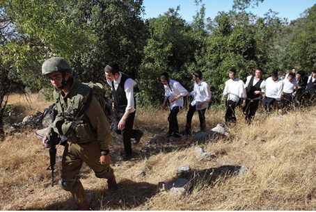 An Israeli soldier escorts ultra-Orthodox Jew