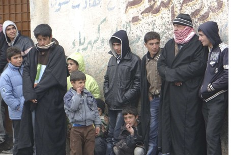 Syrians wait in line to buy bread