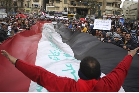Anti-Morsi demonstrator gestures to a crowd o