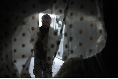 FSA fighter walks through damaged apartment