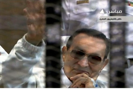 Hosni Mubarak waves from behind bars during h