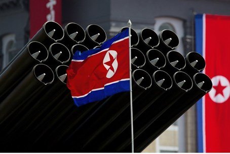 A North Korean flag flies before missiles