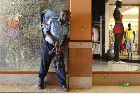 Kenyan police officer takes cover during West