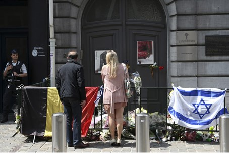 A couple stands by a memorial outside Brussel