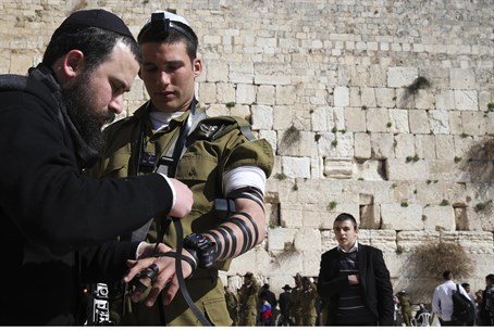 Soldier puts on tefillin at the Kotel (file)