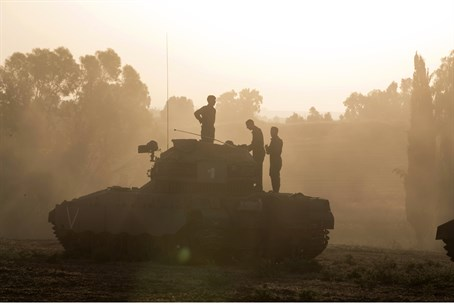 IDF soldiers stand atop an armored personnel