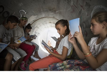 Children sit in a bomb shelter in the souther
